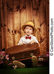 time to travel - Cute little boy in elegant clothes sitting...