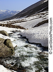 Mountain river with snow bridges in spring sun day. Turkey,...