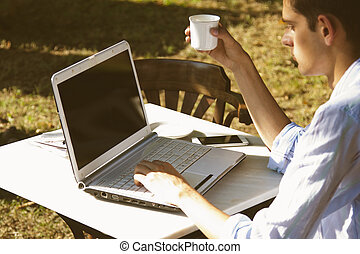 young man with laptop and coffee at sunset