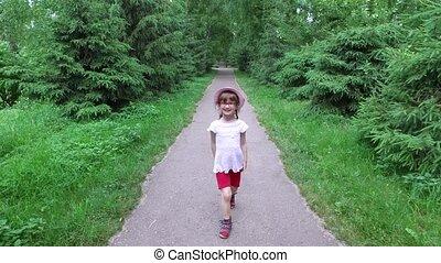 Girl child goes on an asphalt track. The path follows the...