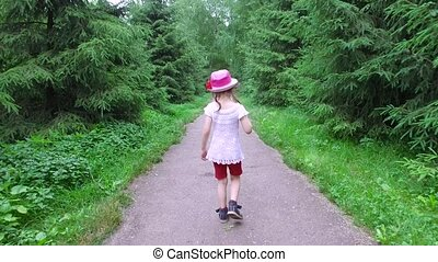 Girl child goes on an asphalt track. The path follows the...