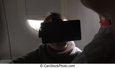 In plane sits a little boy with virtual reality glasses....
