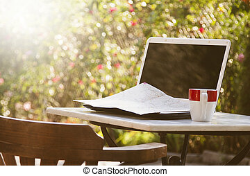 laptop and coffee cup on outdoor table