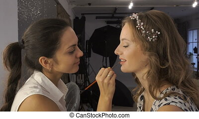 makeup artist doing makeup for the beautiful brunette. lip...