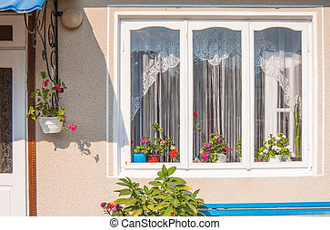 cozy window with a porch and flowers in the rural house