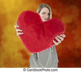 Woman shows heart pillow - Young beautiful woman showing a...
