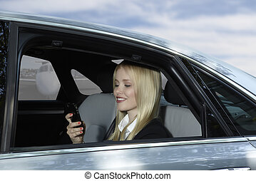 Business Woman in car with mobile phone at airport -...