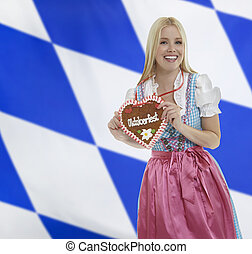 Smiling bavarian woman with Oktoberfest heart - Smiling...