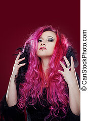 Attractive woman with pink hair in witch image. Halloween style