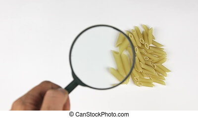 Magnifying glass increases the pasta, motion up, top view