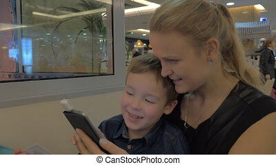 Mother and son paying with mobile card reader - Son helps...