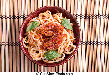 Top view of a thin spaghetti in a brown small wooden bowl -...