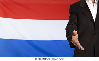Open hand and Netherlands flag in the background -...