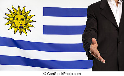 Open hand and Uruguay flag in the background - Businessman...