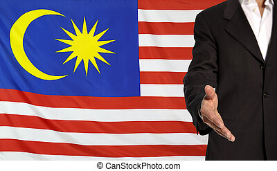 Open hand and Malaysia flag in the background - Businessman...