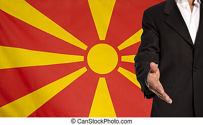 Open hand and Macedonia flag in the background - Businessman...