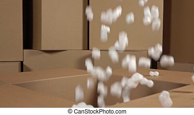 Pouring soft polystyrene pieces into big carton. Shockproof...