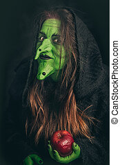 Evil witch holding a rotten apple - Green witch with long...