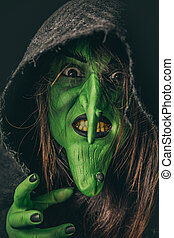 Evil witch casting a curse under her hood - Green witch with...
