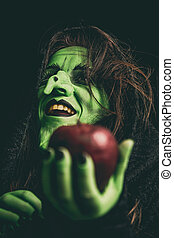 Evil witch laughing - Green witch laughing while holding an...