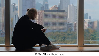 Young woman sitting on the windowsill, using tablet and...