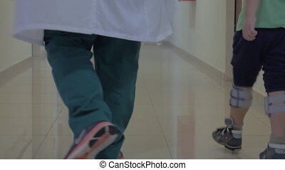 Child and doctor walking in hospital hallway - Back shot of...