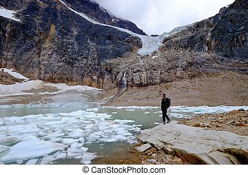 Man hiker in nature by lake with icebergs. - Angel Glacier...