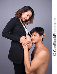 young couple: pregnant mother and happy father on gray...