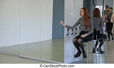 Ginger woman sits on chair in dancing hall and gives...