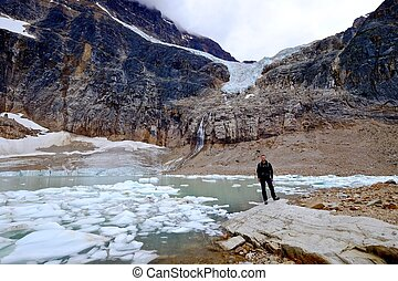 Man ecologist by lake with icebergs. - Angel Glacier at...