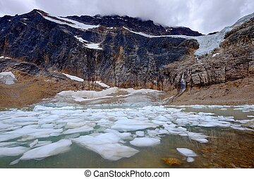 Icebergs in a moraine lake and mountains. - Angel Glacier at...