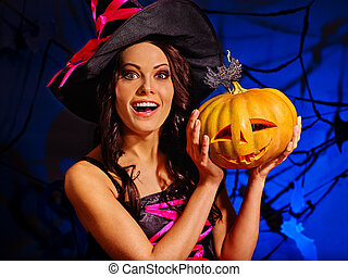 Witch holding pumpkin on Halloween party. - Portrait of...