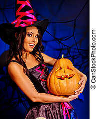 Witch in on Halloween hat holding Jack OLanten pumpkin. -...