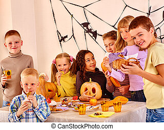 Halloween party with children eating trick or treat. -...