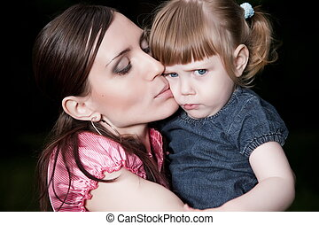 Mother Kissing Daughter Cheek. Close-Up Portrait