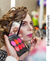 Charming Girl doing make-up in a beauty salon.