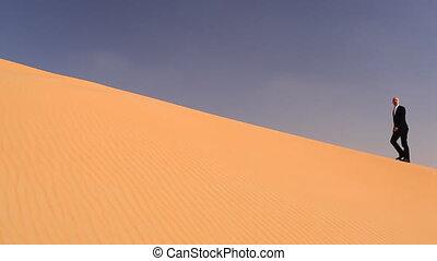 businessman in desert sand - businessman climbing a dune in...