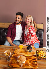 Young Woman And Hispanic Man Sitting In Cafe Hold Orange...