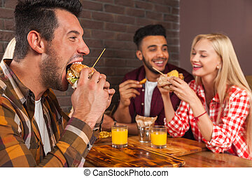 People Group Eating Fast Food Burgers Sitting At Wooden...