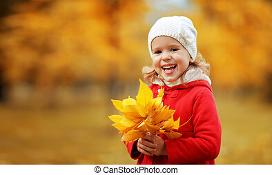 happy child girl laughing with leaves in autumn