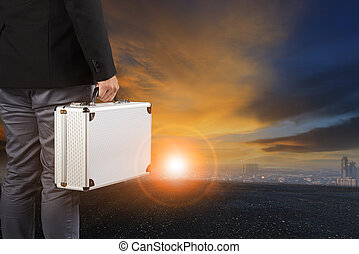 business man and breifcase standing against sun rising sky...