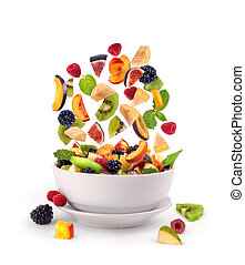 Fresh mixed fruits pieces falling in white bowl of fruit...