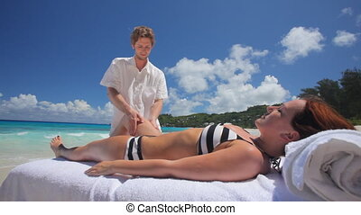 woman in bikini during leg massage - physiotherapist working...