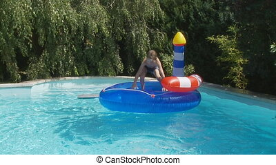 boy on island in pool slo mo - boy having fun on inflatable...