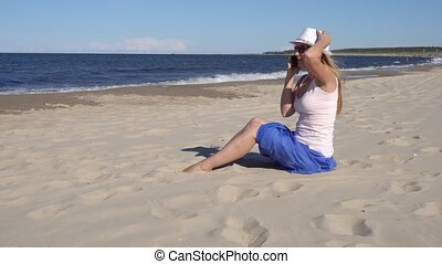 young woman talking by cell phone on the beach