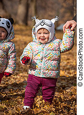The two little baby girls standing in autumn leaves - The...