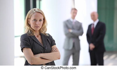 serious looking businesswoman with blurred men in back