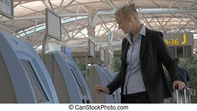 Woman using self check-in machine in the airport - Young...