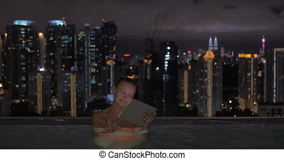 In pool on roof of a hotel in Kuala Lumpur, Malaysia woman working on a tablet