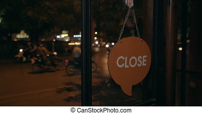 Changing store door sign from Open to Close at night - Woman...